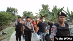 Polisi bersenjata sita barang bukti dari hasil penggeledahan di Pasar Kliwon, Solo, Rabu, 12 Agustus 2015 (Foto: VOA/Yudha)