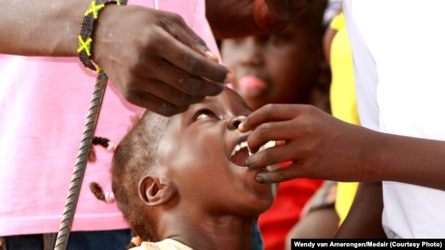 A child is given an oral cholera vaccine dose at the UNMISS Tomping camp in Juba, where tens of thousands of South Sudanese are living in makeshift shelters.