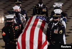 Justice Ruth Bader Ginsburg's flag-draped casket leaves the Statuary Hall at the Capitol