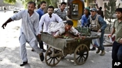 Afghans rush wounded man to treatment after a suicide car bomber strikes outside Supreme Court, Kabul, June 11, 2013.
