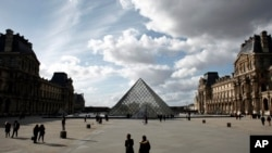 People walk by the Louvre Museum, in Paris, March 13, 2020.
