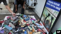 Officials from Indonesia's Child Protection Commission collect sandals sent to their office in Jakarta by outraged citizens as part of a campaign to support a boy who was beaten by police and faces five years in jail for stealing footwear, January 4, 2012