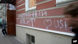 "FILE - A man passes by the office of ""Memorial"" rights group in Moscow, Russia, Nov. 21, 2012. The building has the words ""Foreign Agent (Loves) USA"" spray-painted on its facade."