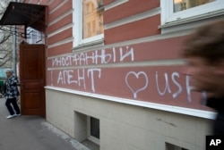"""FILE - A man passes by the office of the """"Memorial"""" human rights group in Moscow, Russia, Nov. 21, 2012. The building has been defaced with the words """"Foreign Agent (Loves) USA"""" spray-painted on its facade."""