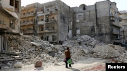 Čovek prolazi kroz porušeni deo Alepa, koji je već neko vreme na meti vladinih vazdušnih udara