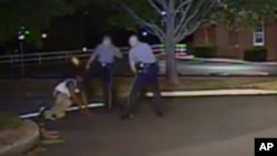 In this Aug. 24, 2013, photo made from a police dash camera video and released by the Dover Police Department, Dover Police Cpl. Thomas Webster, center, kicks Lateef Dickerson in the face as Dickerson is following orders to get on the ground during an arr