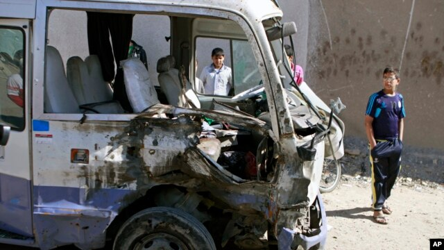 Children inspect a bus destroyed in a car bomb attack in the Shi'ite stronghold of Sadr City, Baghdad, Iraq, March 19, 2013.