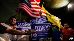 Mideast Israel Trump: Israelis wave flags and hold signs during a rally, sponsored by Republicans Overseas Israel, a local organization that encourages American expatriates to cast absentee ballots for Republican presidential candidate Donald Trump, in Je