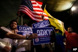 FILE - Israelis wave flags and hold signs during a rally in Jerusalem in support of Donald Trump.