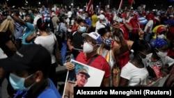 Seorang pria membawa foto mantan presiden Kuba dan Sekretaris Pertama Partai Komunis, Raul Castro, dalam unjuk rasa terkait kekhawatiran pandemi COVID-19 di Havana, Kuba, 17 Juli 2021. (Foto: Alexandre Meneghini/Reuters)