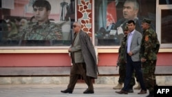 Afghan First Vice President Abdul Rashid Dostum, left, walks at his headquarters in Sheberghan, capital of northern Jowzjan province, July 28, 2015.