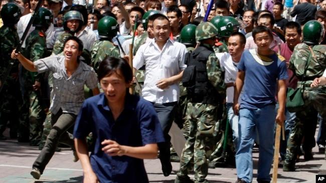 资料照:手持棍棒的汉族人冲破武警人墙,试图攻击维族地段。(2009年7月7日)