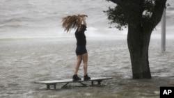 當艾薩克颶風8月28日快要在新奧爾良地區登陸的時候,一名婦女站在龐恰特雷恩湖湖畔沿湖公路上幾乎被巨浪淹沒的長椅上。