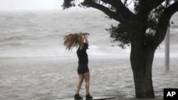 当艾萨克飓风8月28日快要在新奥尔良地区登陆的时候,一名妇女站在庞恰特雷恩湖湖畔沿湖公路上的一个部分被巨浪淹没的长椅上