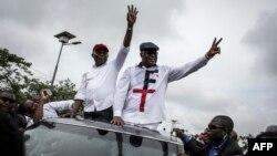 Félix Tshisekedi ,à droite, leader de l'Union pour la démocratie et le progrès social (UDPS) et son allié de l'Union pour la nation congolaise (UNC), Vital Kamerhe, à gauche, saluent leurs partisans après leur retour à Kinshasa, le 27 novembre 2018.