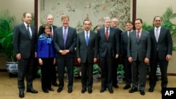 Myron Brilliant, fourth left, executive vice president and head of International Affairs at the U.S. Chamber of Commerce, Chinese State Councilor and Foreign Minister Wang Yi, fifth left, and other delegates take a group photo ahead of a meeting at the Ministry of Foreign Affairs