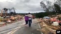 Warga berjalan di antara puing-puing yang berserakan pasca dihantam tornado di Lee County, Alabama, Minggu, 3 Maret 2019.