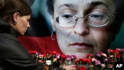 FILE - A woman places flowers before a portrait of slain Russian journalist Anna Politkovskaya, in Moscow.