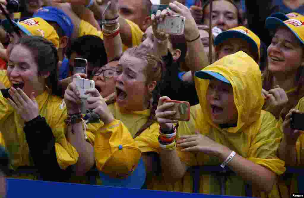 Pilgrims react as they take pictures of Pope Francis during the World Youth Days in Krakow, Poland.