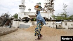 FILE - A girl walks past a destroyed mosque in the town of Mararaba, after the Nigerian military recaptured it from Boko Haram, in Adamawa state, May 10, 2015.