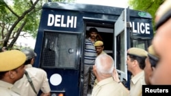 FILE - A man is escorted out of a police van outside a court in New Delhi.