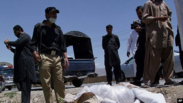 Pakistani security officials stand next to the covered body of Red Cross worker Khalil Dale in Quetta April 29, 2012.