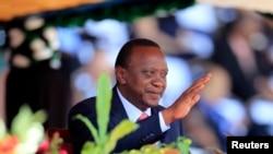 ປະທານາທິບໍດີ Uhuru Kenyatta ແຫ່ງເຄນຢາ ຍົກມືຂຶ້ນ ຂະນະທີ່ໄປຮ່ວມວັນວີລະຊົນ ທີ່ສະໜາມກິລາແຫ່ງຊາດ Nyayo ໃນນະຄອນຫຼວງໄນໂຣບີ (20 ຕຸລາ 2013)