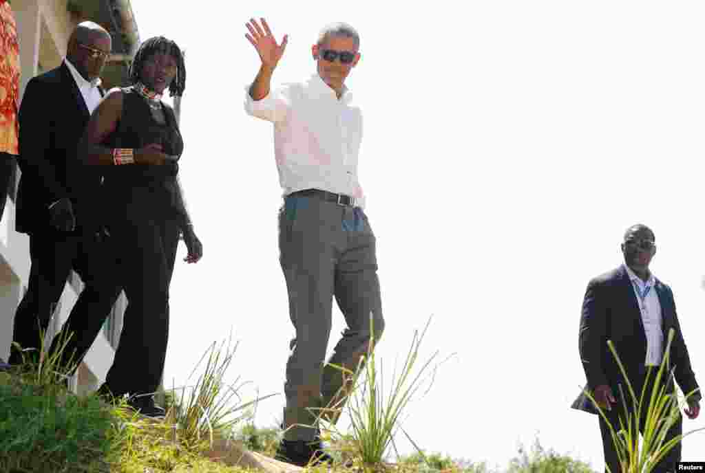 Former U.S. President Barack Obama waves to photographers as he tours the Sauti Kuu resource center near his ancestral home in Nyangoma Kogelo village in Siaya county, western Kenya. With him is Auma Obama.