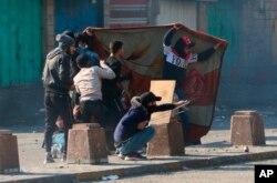 Para pemrotes anti-pemerintah berlindung selama bentrokan dengan pasukan keamanan di Baghdad, Irak, Jumat, 31 Januari 2020. (AP Photo / Hadi Mizban)