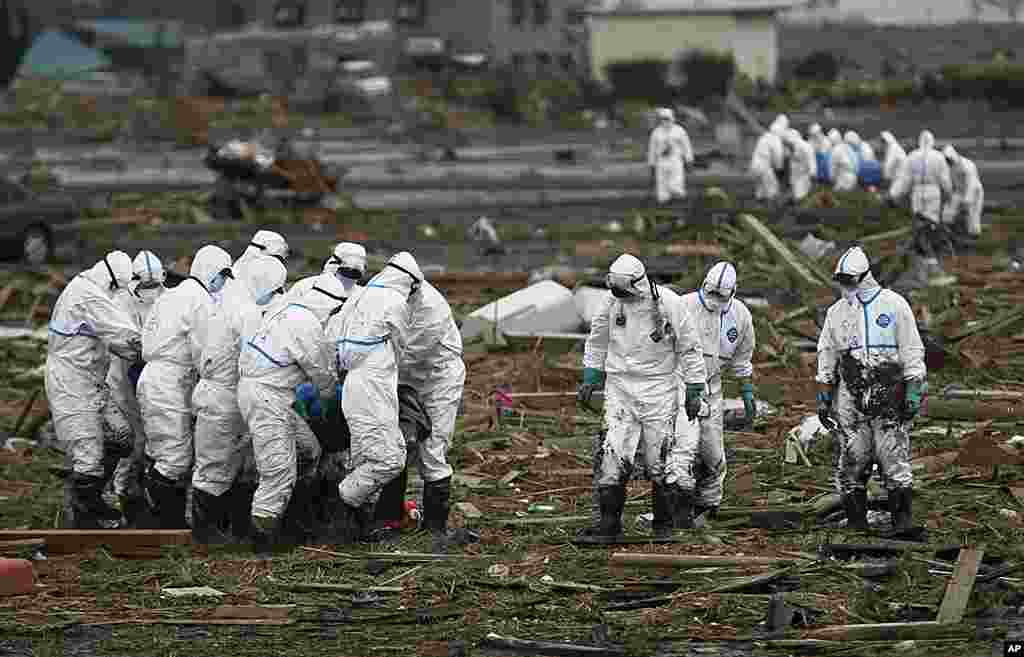 A group of Japanese police officers wearing suits to protect them from radiation carries a victim as another group carries another body in the background while searching for missing people in Minami Soma, Fukushima Prefecture, April 8, 2011. (AP)
