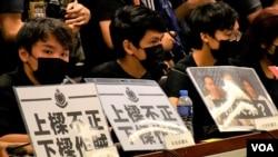 多名元朗民主派區議員在座位前放上抗議警方的標語。(美國之音湯惠芸)