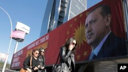 "People walk past a huge billboard with an image of Turkey's President Recep Tayyip Erdogan that reads ""Yes"" in Turkish, in Ankara, Turkey, March 22, 2017. A referendum set for April 16 could boost Erdogan's powers."