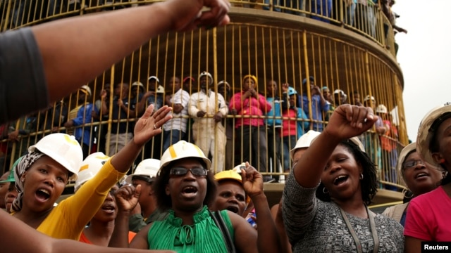 Miners sing church hymns as they mourn their colleagues outside a shaft at Harmony Gold's Doornkop mine near Johannesburg, Feb. 6, 2014.