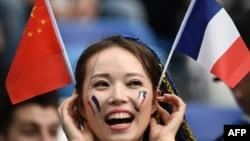 """Một cổ động viên với cờ Trung Quốc và Pháp trong trận đấu giữa """"những chú gà trống gaulois"""" và Uruguay hôm 6/7."""