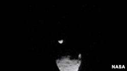 Gambar dari video yang diambil menunjukkan bulan Phobos melintas di depan bulan Deimos.