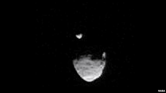 A screenshot shows Martian moon Phobos passing in front of smaller moon, Deimos.