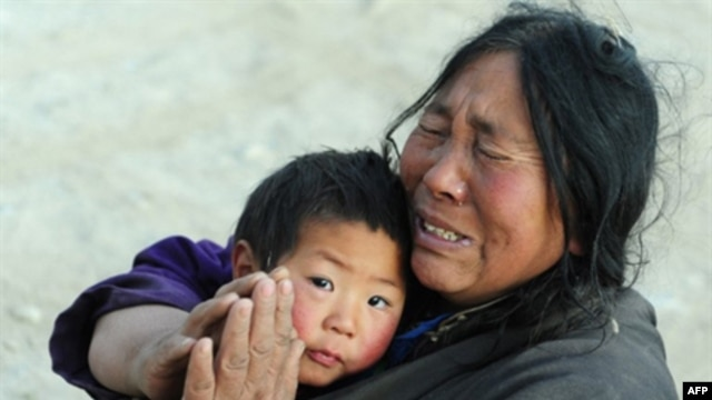 An earthquake survivor gestures in prayer while holding onto her nephew. (file)