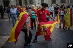 Men perform a mock bullfighting game after a mass rally against Catalonia's declaration of independence, in Barcelona, Spain, Oct. 29, 2017.
