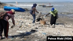 Para relawan memunguti sampah plastik yang banyak berserakan di pantai Kenjeran sisi timur Jembatan Suramadu (Foto: VOA/Petrus Riski)