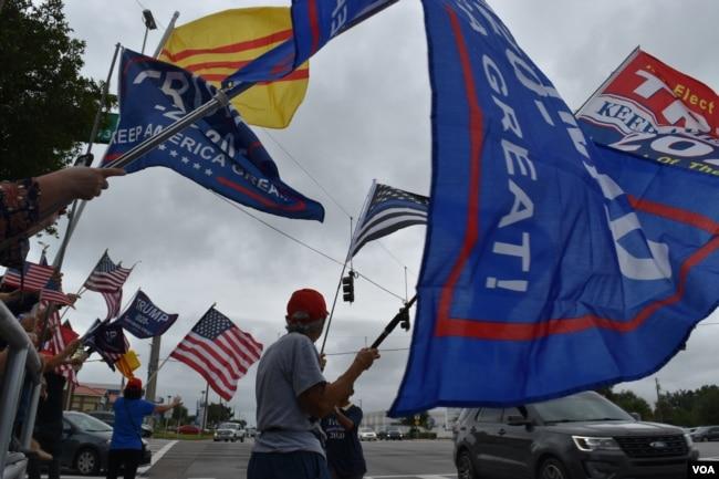 Những người Mỹ gốc Việt cùng những người Mỹ khác tụ tập tại một giao lộ đông đúc để vẫy cờ và giơ biểu ngữ ủng hộ Tổng thống Trump, thành phố St. Petersburg, bang Florida, ngày 4 tháng 10, 2020.