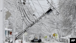A police vehicle blocks a road near downed power lines, March 8, 2018, in Natick, Massachusetts.