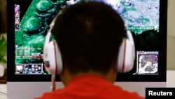 A man plays a computer game at an internet cafe in Beijing May 9, 2014. As growing numbers of young people in China immerse themselves in the cyber world, spending hours playing games online, worried parents are increasingly turning to boot camps to crush