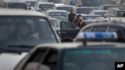 Motorists come out from their vehicle to check as the traffic stand still at a city road in Beijing, China, Tuesday, Nov. 22, 2011.