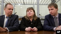 FILE - Oksana Sevastidi, with her lawyers, awaits a court hearing in the Russian Supreme court in Moscow, Russia, March 15, 2017. Sevastidi was convicted of treason for sending text messages about military movements near Georgia's breakaway republic of Abkhazia. Putin pardoned Savastidi that month, and pardoned two other women serving prison sentences for the same offense Saturday.