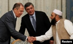 FILE - Russian Foreign Minister Sergei Lavrov welcomes member of Taliban delegation Alhaj Mohammad Sohail Shaina during the multilateral peace talks on Afghanistan in Moscow, Russia, Nov. 9, 2018.