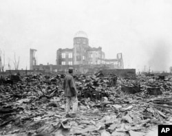 FILE - In this Sept. 8, 1945 file photo, an allied correspondent stands in the rubble in front of the shell of a building that once was a movie theater in Hiroshima, Japan, a month after the first atomic bomb ever used in warfare was dropped by the U.S., Aug. 6, 1945.