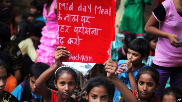 Indian children hold placards as they participate in a protest organized by non-governmental organization Bachpan Bachao Andolan, or Save Childhood Movement, against the death of schoolchildren after eating free midday meal, July 20, 2013.