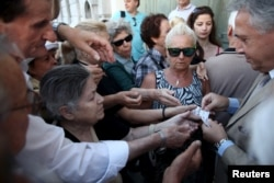 Pensioners are given priority tickets by a National Bank branch manager (R), as they wait to receive part of their pensions in Athens, Greece July 13, 2015.