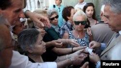 Giám đốc chi nhánh Ngân hàng Quốc gia Hy Lạp cấp phiếu ưu tiên lãnh tiền cho người về hưu ở Athens, ngày 13/7/2015.