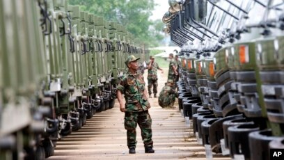 FILE PHOTO - A Cambodian army soldier looks at Chinese military vehicles displayed before a handover ceremony at a military airbase in Phnom Penh, Cambodia, Wednesday, June 23, 2010.